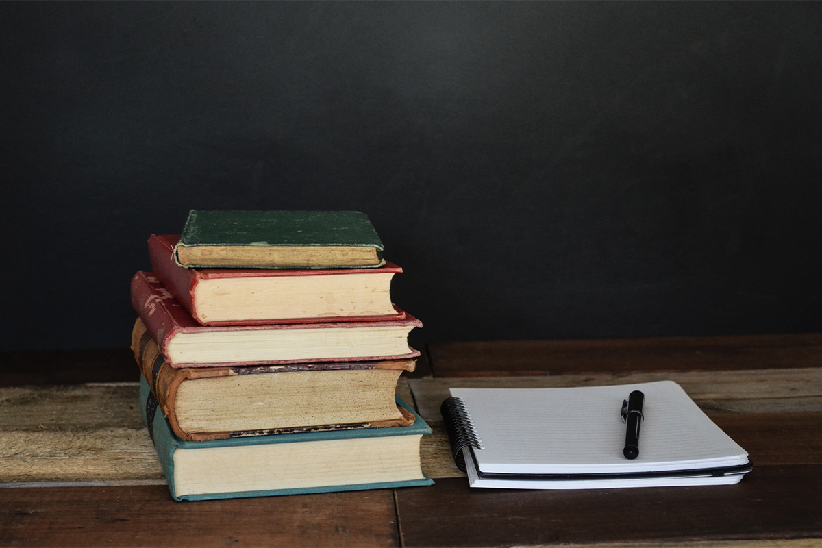 Books and notebook on the table with a pen over the notebook